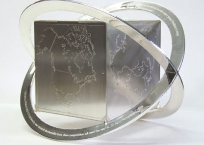 ox, Hinged, 925 Silver, Six photoetched 'Continent' panels attached to wood box and supported within two silver engraved bands. With 100 1.2 cubic zirconiums set in apropriate  capital citys. Band diameters 380mm.
