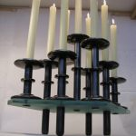 """9-light Centrepiece Nine independent candlesticks locating on a glass platform.  Fixed 'studs' on the glass give locations for the nine independently useable candlesticks any of which may be lifted off and stood on the table or elsewhere and offering maximum flexible use.  So much for silver that doesn't require to be cleaned.  375mm (14.75"""") long x 265mm (10.5"""") wide (the glass), Sterling silver all darkly oxidised, 2007"""