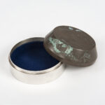 A sterling silver container, blue baize lined and patinated lid.