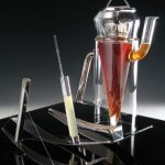 Tea Pot in borosilicate glass (Pyrex) with conical silver tea diffuser, lid and silver handle. Milk jug in silver, lemon juice dispenser in silver and glass, sugar column in silver and glass with steel wire in tension holding the column. Tea Pot 260mm H.  Glass by Chemglass Ltd. Photo A Nelki.