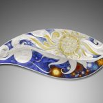 Celebration dish Materials: Standard Silver, Champleve and Basse Taille Enamel  Size:  50cms in length  Decorative Dish commissioned to mark and celebrate a marriage, the imagery is that of Sun, Moon, and Fireworks