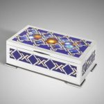 A silver and enamel box with firework design on lid. Interior lined with fiddleback sycamore and padauk.  Approx. length 31.5 cmm x width 17.5 cm