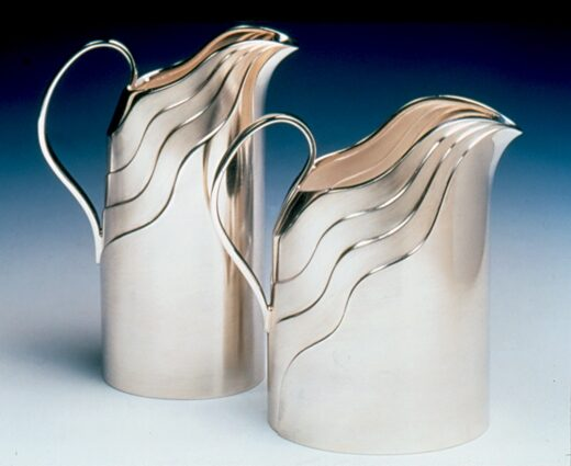 Curvilinear Jugs A related series of vessels with a flowing curvilinear formation based on the puring action of liquid. The sharply modelled lines are created as a result of the overlap technique which is used to build up the body, section by section.  The surface detailing and textural quality of the finished designs evolve in a natural manner, directly from the process of construction.  Heights 450mm/420mm. Capacity 250ml/275ml