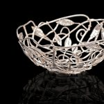 A fruit or bread bowl of intertwined silver branches and leaves